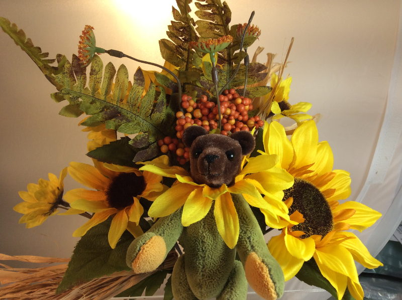 Teddy bear with flower ruff in front of flower arrangement