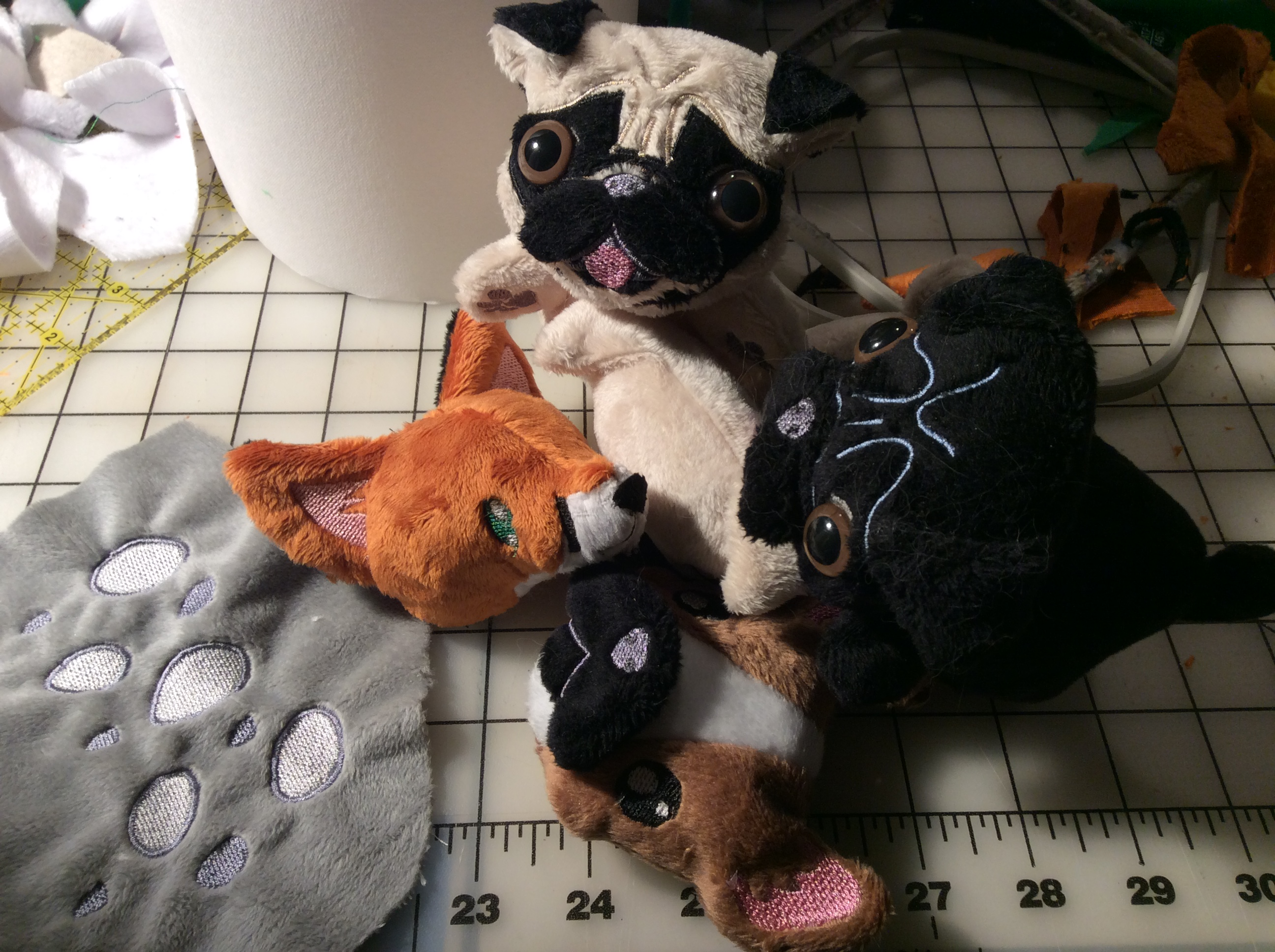 Three pugs, a fox head, a frenchie head, and a piece of fabric with some embroidered spots.