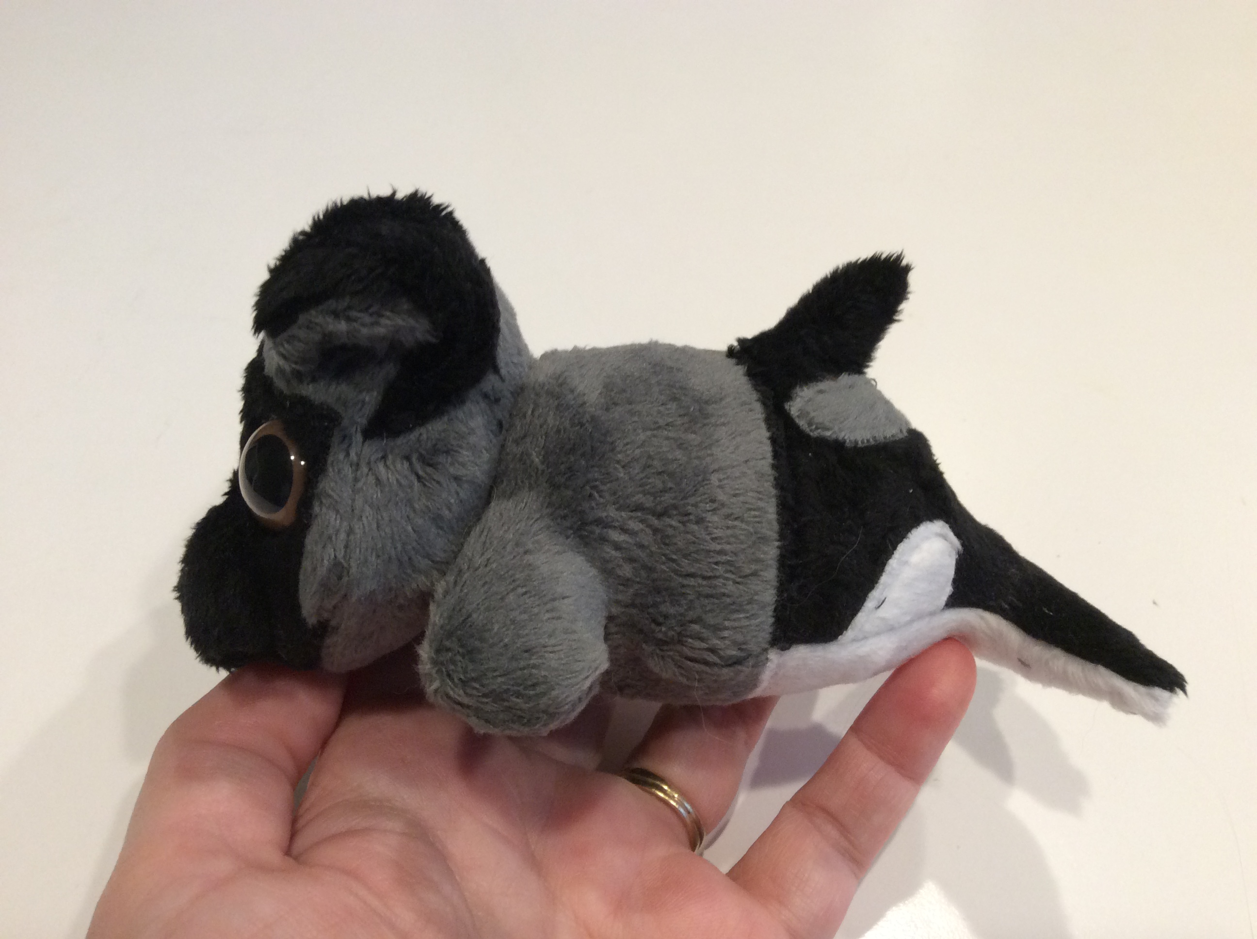 Side view of a plush pug/orca mermaid.