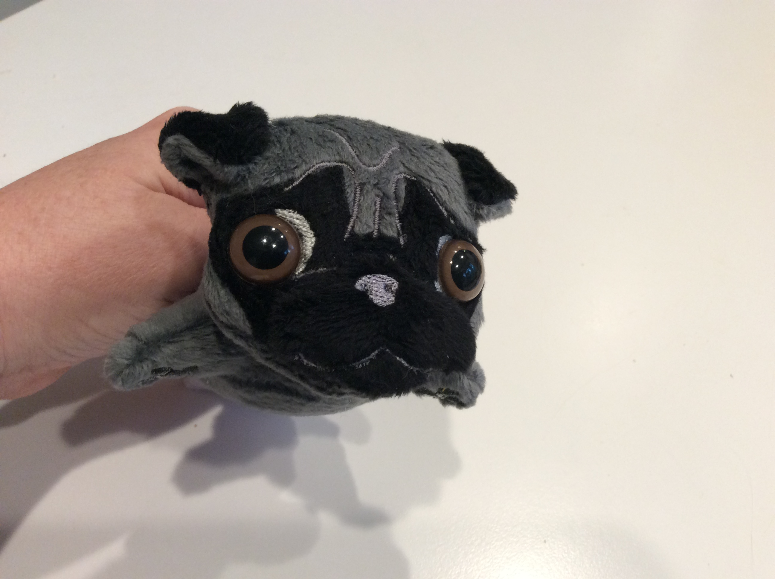 Another view of a plush silver pug face
