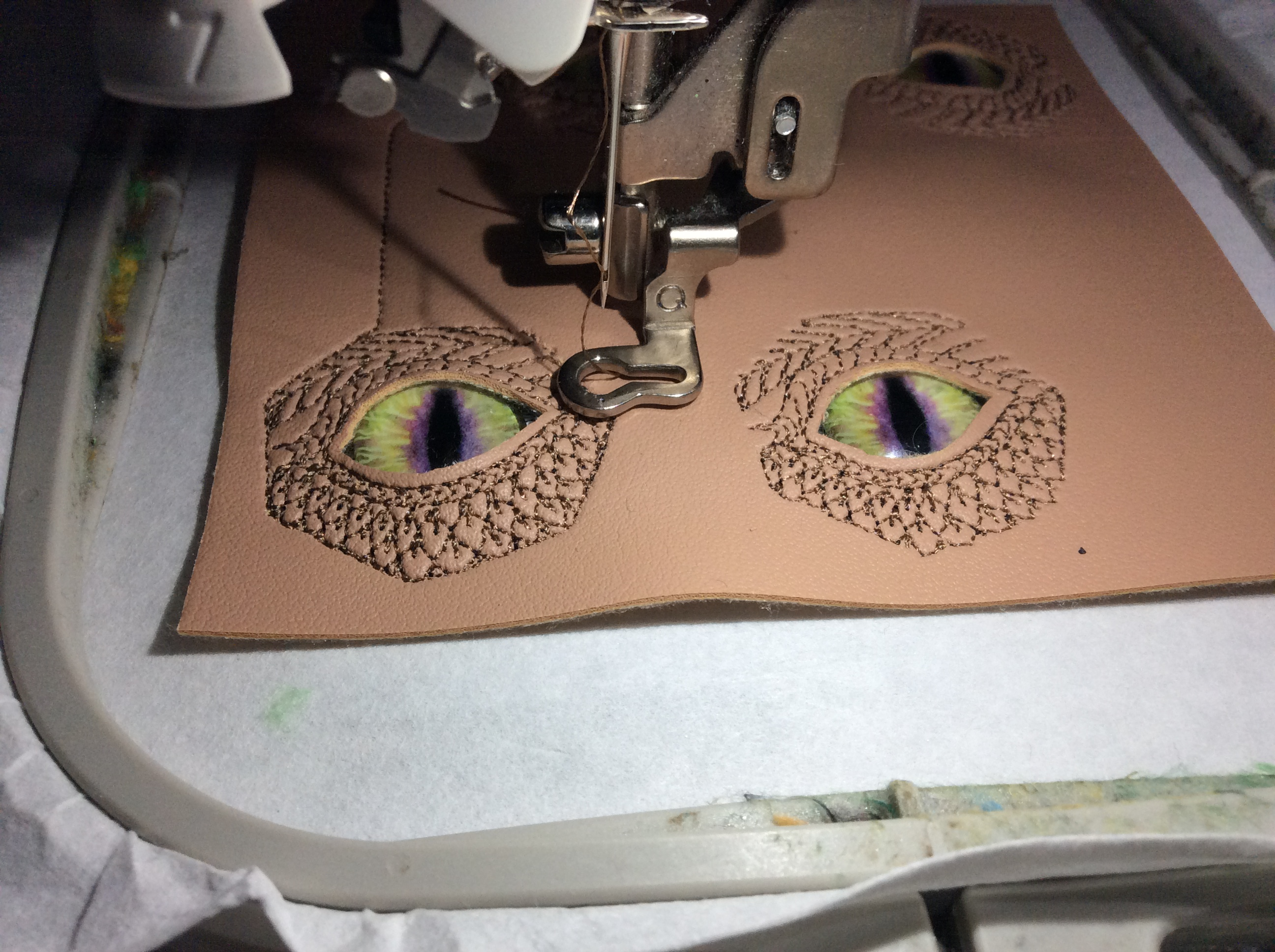 An embroidery machine embroidering scales around large glass cat-eye cabochons.
